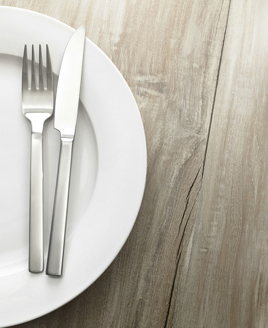 Photo of an empty plate, fork, and knife on a wooden table